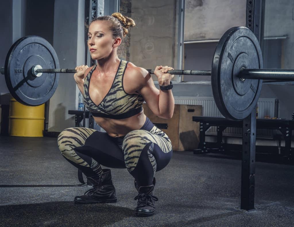 Kvinne som utfører styrkeøvelsen knebøy.