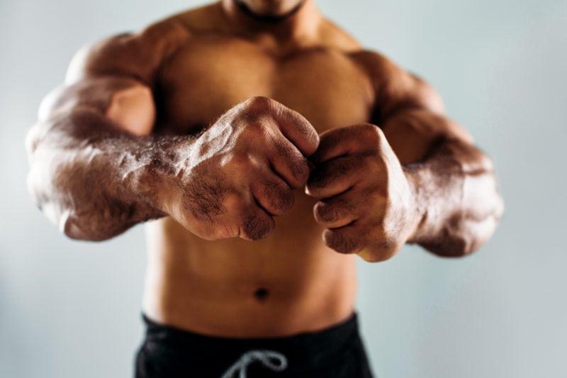 Mann som strammer musklene