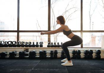 Kvinne som tar knebøy uten hofteforskyvning