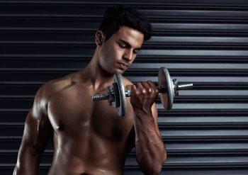 Mann som trener biceps med manual