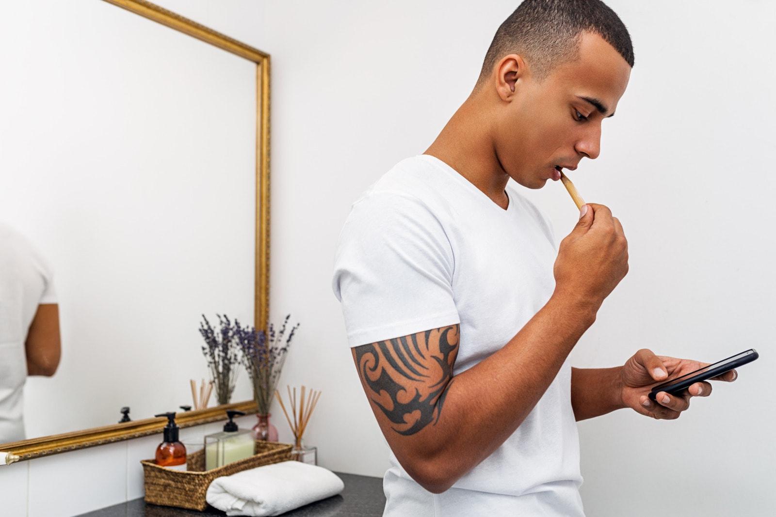 Stående glute kickbacks mens du pusser tennene
